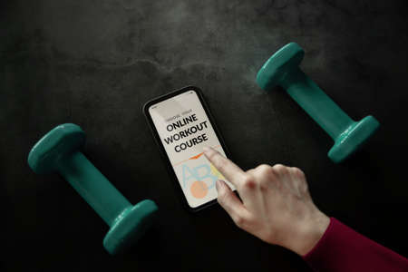 Learning Online Workout Concept. Young Woman using Mobile phone to choosing an Exercising Course. Dumbbell on the Concrete Floor Imagens