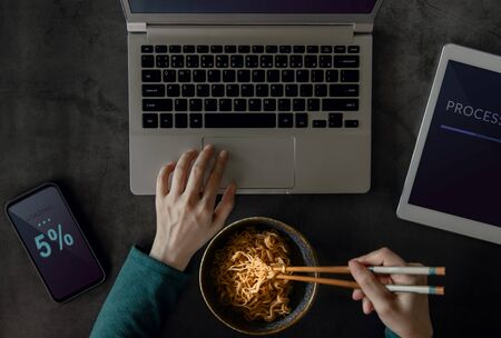 Woman Eating Noodle while Working on Computer Laptop, Mobile Phone and Tablet. Top View. Unhealthy Food in a Busy Working Day. a Workaholic Habits