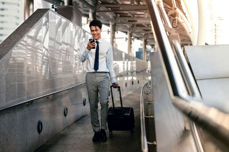 Smiling  Passenger Businessman Using Mobile Phone while Walking with Suitcase in the Airport or Public Transportation Station. Lifestyle of Modern People. Full Length