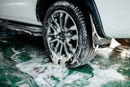 Manual Car Wash on Soap Process. Keep Clean for Driver and Passenger. Focus on Wheel Imagens