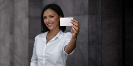 Business Card Mockup Image. a Smiling Mixed Races Business Woman showing a Blank White Card