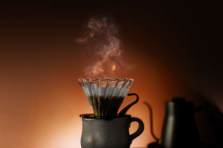 Coffee Drip Concept. Dripper, Mug and Kettle with Motion Steam. Dramatic lighting in Studio