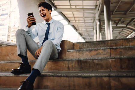 Smiling Young asian Businessman Using Mobile Phone.