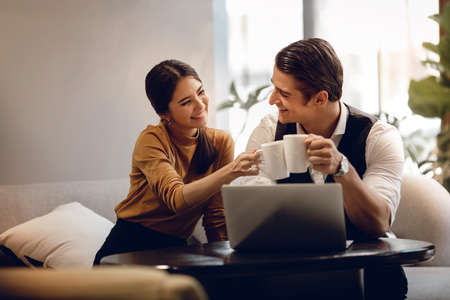 Young Couple Working Together on Computer Laptop in Cafe. Multiethnic Motivated Teamwork. Happy Business People Imagens