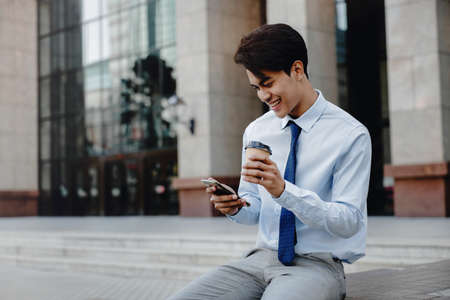 Smiling Young asian Businessman Using Mobile Phone in the City.