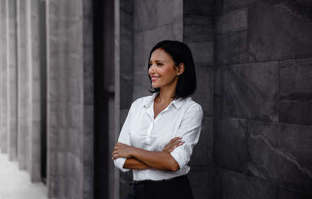 Portrait of a Smiling Mixed Races Business Woman, Crossed Arm and Looking away in Urban City Imagens