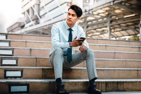 Young Striving Asian Businessman Sitting on Staircase in the City. hand holding a Mobile Phone