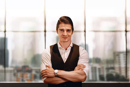 Portrait of a Smiling Caucasian Businessman, Crossed Arm and Look into the Camera. Blurred Office Building in the City as background