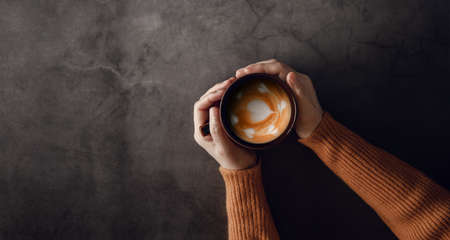 Young Woman with Hot Coffee Latte Cup in Hand. Top View Imagens