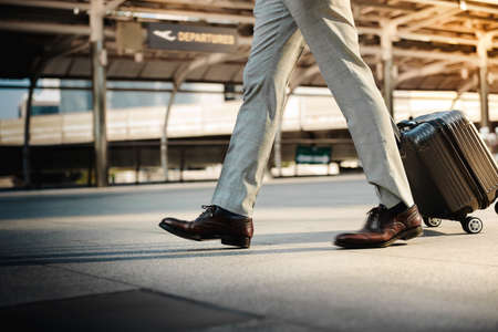 Low Section of Passenger Businessman Walking with Suitcase at the Entrance Walkway in Airport. Focus on Luggage. Low Angle View Imagens