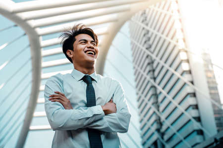 Portrait of a Young Asian Smiling Businessman in the City. Crossed Arms and looking away
