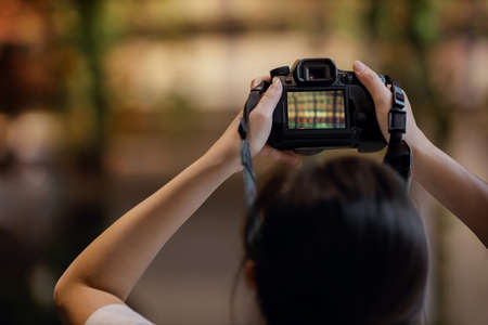 Young Photographer Woman Raise Up a Camera to Taking Photo. Selective Focus on Camera Imagens