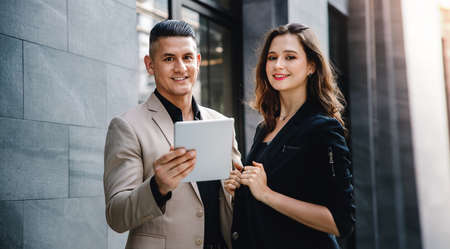 Teamwork or Work Together Concept. Portrait of Businessman and Business Woman Working on Tablet outside the Office