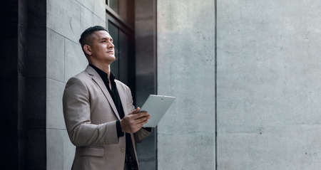 Portrait of a Young Striving CEO or Leader Working on Tablet.  Businessman Standing at the City and Looking away