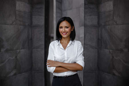 Portrait of a Smiling Mixed Races Business Woman, Crossed Arm and Look into the Camera
