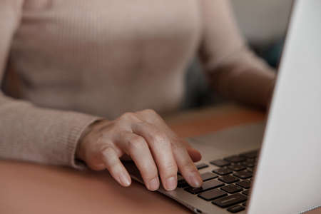 Young Woman Working on Computer Laptop. Closeup shot and Cropped Image