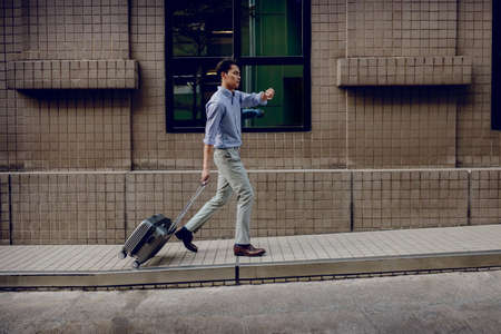 Hurrying to get on a Business Trip. Stressed Passenger Businessman Walking with Suitcase in the City, Worried Face while Seeing Watch. Full Length. Rush Time