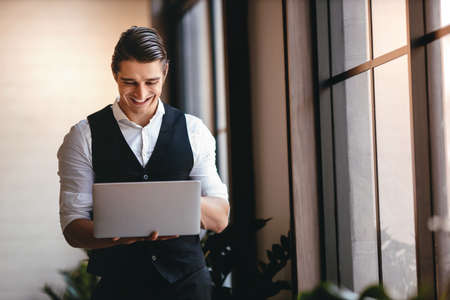 a Young Caucasian Businessman Working on Computer Laptop in the Modern Workplace. Smiling Businessman Standing by the Window Imagens