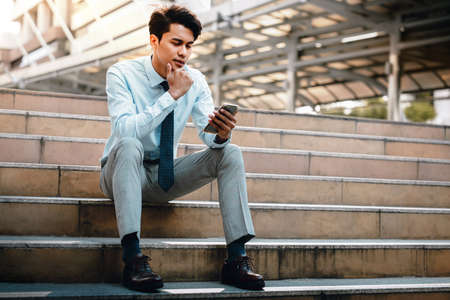 Young Striving Asian Businessman Using Mobile Phone in the City. Sitting on Staircase. Reading Seriously topic via Smartphone Фото со стока