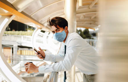Young Asian Businessman Wearing a Surgical Mask and Using a Smart Phone in City. Healthcare in New Normal Lifestyle Concept. Looking at the Camera