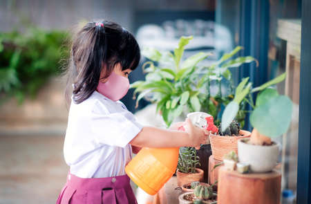 Happy Asian Girl wearing a Surgical Protection Mask while Enjoying in Garden at School or Home, a Child in Student Uniform is Watering Plant Фото со стока