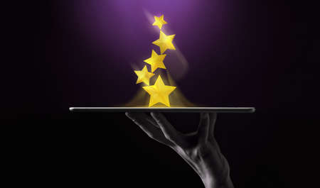 Success in Business or Personal Talent Concept. Hand Raise Up a Digital tablet with Golden Five Star Awards