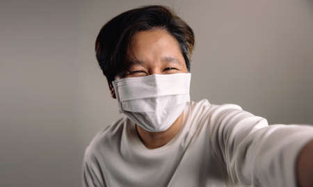 Portrait of a Happy Person, Wearing a Surgical Mask and Taking Selfie against the White Wall 版權商用圖片