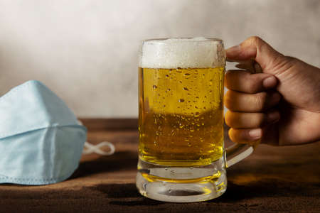 Drinking Beer in Covid-19 Situation Concept. Take off a Surgical Mask on Table before Drinking a Glass of Beer Standard-Bild - 155680789