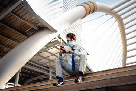 Young Asian Businessman Wearing a Surgical Mask and Using a Smart Phone in City. sitting on Staircase. Healthcare in New Normal Lifestyle Concept