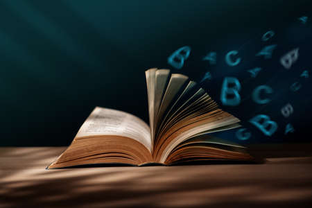 Reading, Education, Learning Concept. Manipulation Photo of Opened Book with Blowing Alphabet on Table