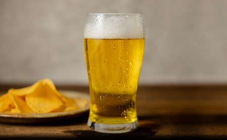 Glass of Beer and plate with Potato Chips on Table. Drinking Beer at Home or Cafe