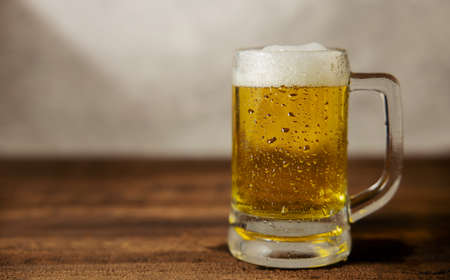 Glass of Beer on Table. Drinking Beer at Home or Cafe at Day Фото со стока