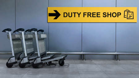 Airport Sign for Duty Free Shop inside the Terminal Building. Travel and Transportation Concept. Blurred Baggage Carts as foreground Standard-Bild