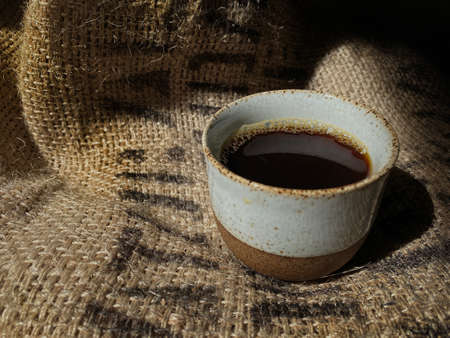 Hot Coffee in Traditional Ceramic Cup on Vintage Coffee Beans Sack 版權商用圖片