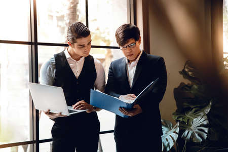 Two Businessman Working Together on Computer Laptop in Creative Workplace. Standard-Bild