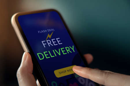Free Delivery Promotion Concept. Digital Marketing Strategy. Closeup of Customer Woman Using Mobile Phone to Shopping Online. Free Shipment Campaign show on Screen