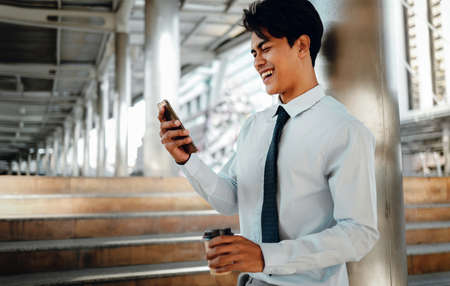 Portrait of a Smiling Young Asian Businessman Using Mobile Phone in the City Standard-Bild - 156318883