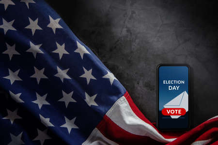 Election Day in United States Concept. Online Vote show on Mobile Phone Screen. Smartphone Lying on Cement background and USA Flag nearby. Top View Standard-Bild