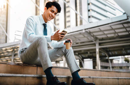 Smiling Young Asian Businessman Using Mobile Phone in the City. Sitting at the Staircase