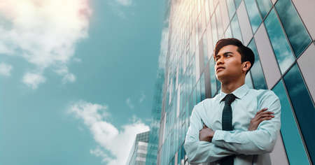 Portrait of a Striving Young Asian Businessman in the City. Crossed Arms and looking up into the Sky. Modern Office Building as background
