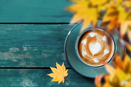 Drinking Coffee in Fall and Autumn Season. Hot Coffee Latte Cup on Blue Wooden Table. Top View. Focus on Latte Art in Heart Shape. blurred Yellow Maple Leaf as foreground