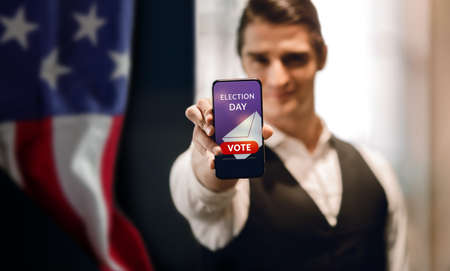 Election Day in United States Concept. Young Man presenting Online Vote on Mobile Phone Screen. USA Flag as background
