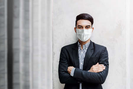 Portrait of Asian Young Businessman Wearing Surgical Mask and standing at the Wall, Smiling and Crossed Arms, Looking at camera