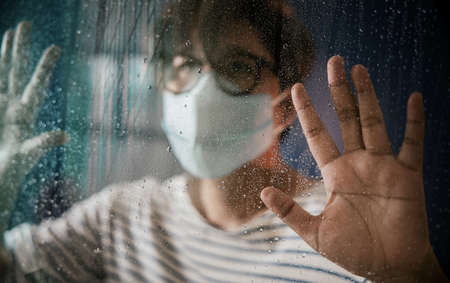 Hopeful in Coronavirus Situation Concept. Sad Person Wearing Surgical Mask in House, Looking Outside  through the Glass Window in Rainy Day. Selective Focus on Hand and Raindrop Standard-Bild