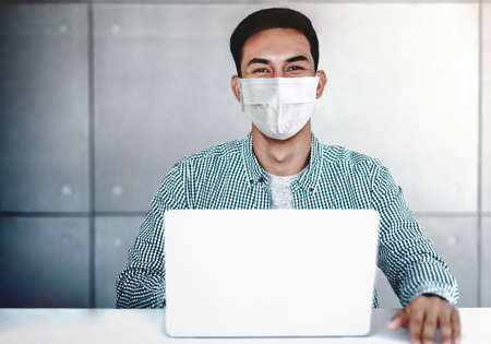Asian Young Businessman Wearing Surgical Mask in Office. Sitting on Desk while Working on Computer Laptop. Smiling and Looking at camera Standard-Bild - 157975321