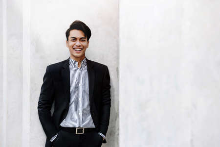 Portrait of Smiling Young Asian Businessman in Casual Suit. Standing in the City. Looking at Camera. a Happy Friendly Man