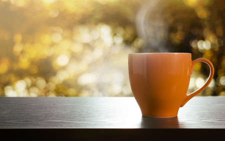 Cup of Hot Coffee on Table. Relaxation Concept. Side View. Golden bokeh as background