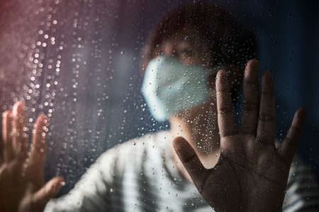 Hopeful in Coronavirus Situation Concept. Sad Person Wearing Surgical Mask in House, Looking Outside  through the Glass Window in Rainy Day. Selective Focus on Hand and Raindrop Standard-Bild - 158221706