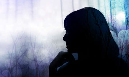 Side View of a Sadness Woman. Hand on Chin, Silhouette and Double Exposure style, Mixed by blurred light Bokeh and Dry Tree Branch