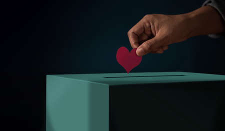 Donation Concept. Hand putting a Red Heart paper into a Donate Box. Metaphor photo. Dark tone